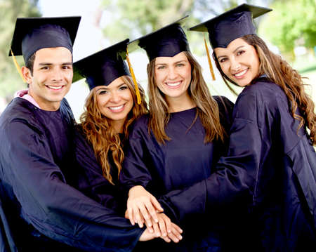 graduado: Grupo de estudiantes en su graduaci�n con las manos juntas - el trabajo en equipo los conceptos