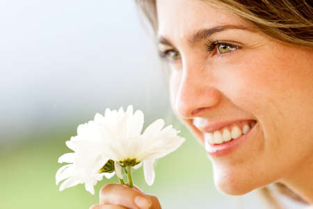 smell: Beautiful woman portrait smelling a flower and smiling