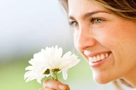 olfato: Hermosa mujer retrato de oler una flor y sonriente Foto de archivo