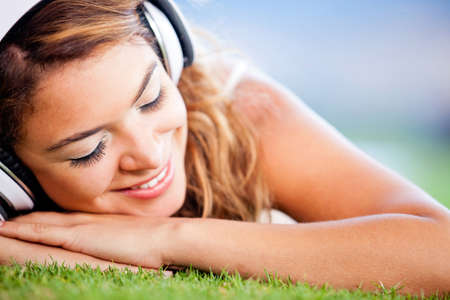 Relaxed woman lying on the floor and listening to music  photo