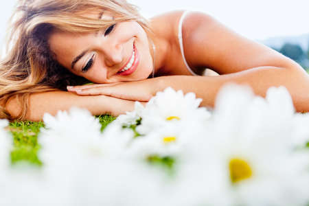 Beautiful woman lying on a garden of daisies photo