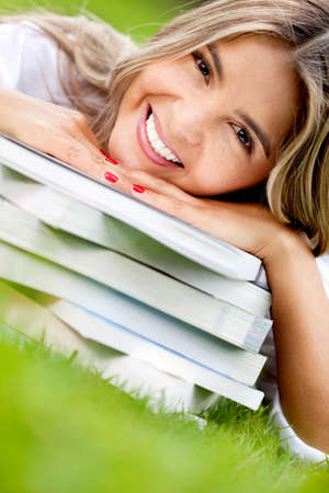 Girl studying outdoors with a pile of books and smiling  photo