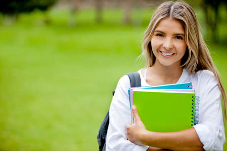 latin students: Beautiful college student holding notebooks and smiling