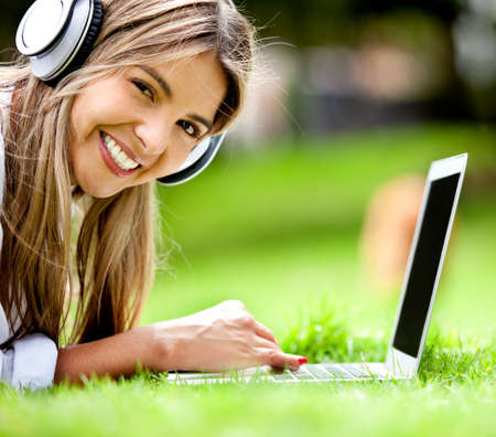 earbud: Happy woman downloading music outdoors with laptop and headphones