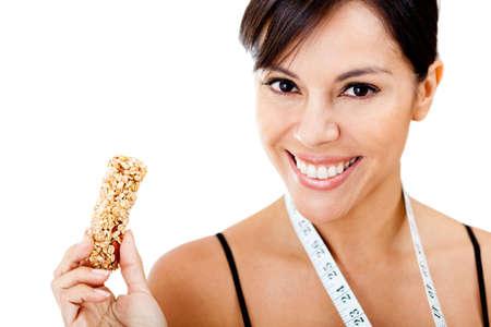 barra de cereal: Mujer sana de comer la celebraci�n de barra de granola - aislados en un fondo blanco Foto de archivo