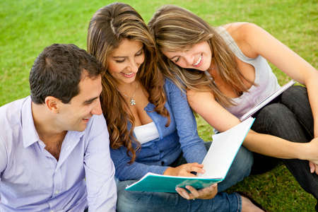 Group of friends holding notebooks and studying outdoors  photo