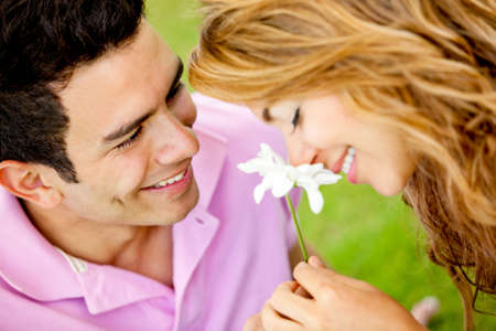 adult dating: Romantic couple on a date and man giving a flower to his girlfriend