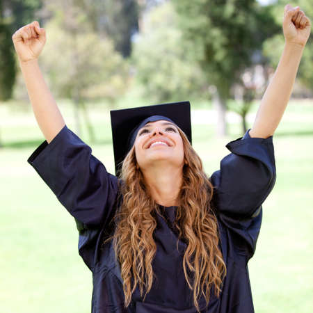 graduado: Estudiante feliz mujer el d�a de su graduaci�n con los brazos arriba Foto de archivo