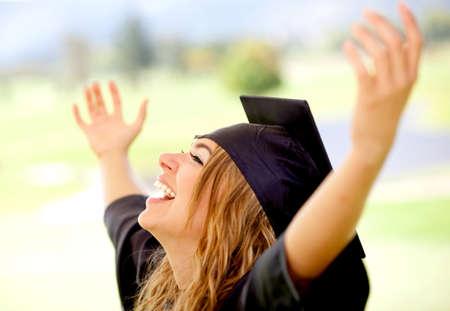 absolwent: Happy absolwenta kobieta z bronią w górę obchodzi