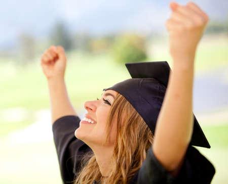 absolwent: Kobieta absolwent z broni do sukcesu w edukacji Zdjęcie Seryjne