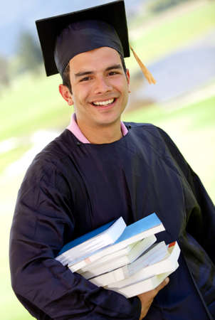 Male graduation student carrying a pile of books and smiling  photo