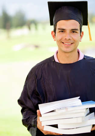 Male graduate in graduation gown holding books  photo