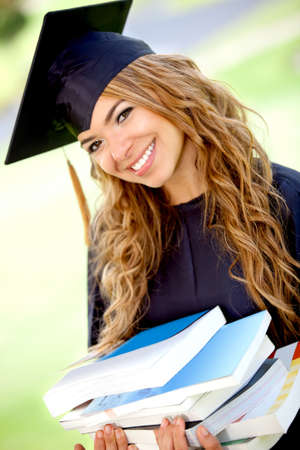 Female graduation student carrying a pile of books and smiling photo