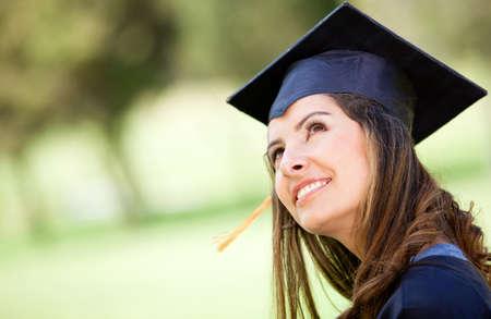 graduacion de universidad: Retrato de un graduado femenino pensativo mirando hacia arriba