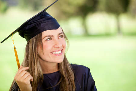 Pensive graduation student looking up outdoors and smiling photo