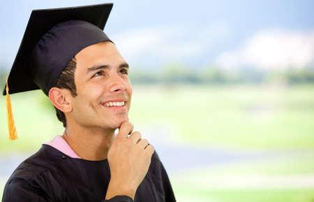 graduacion de universidad: Hombre pensativo de la graduación que llevaba un birrete y mirando hacia arriba Foto de archivo