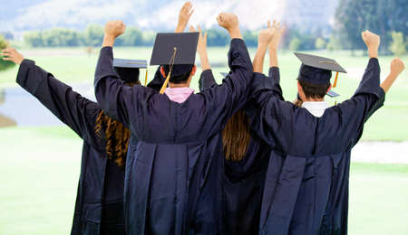 Excited group of people on their graduation day with arms up  Stock Photo - 12393784