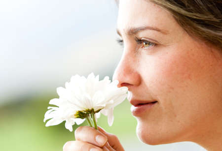 Portrait of a beautiful woman smelling a flower  photo
