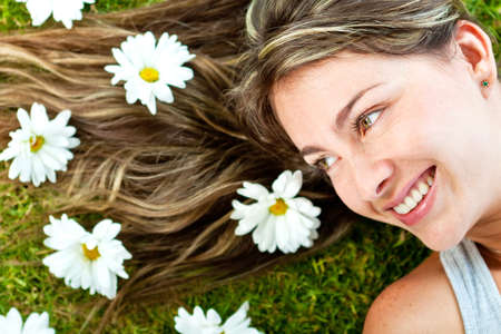 Woman with beautiful blond hair in a garden of daisies    photo