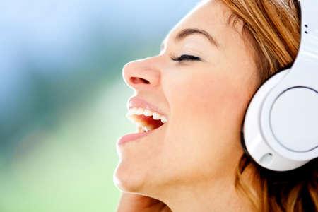 personas cantando: Mujer cantando con los auriculares y disfrutar de la m�sica Foto de archivo