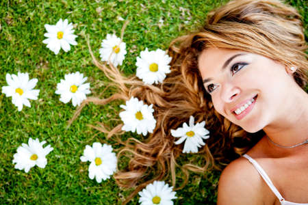 Thoughtful woman lying on a flower garden and smiling  photo