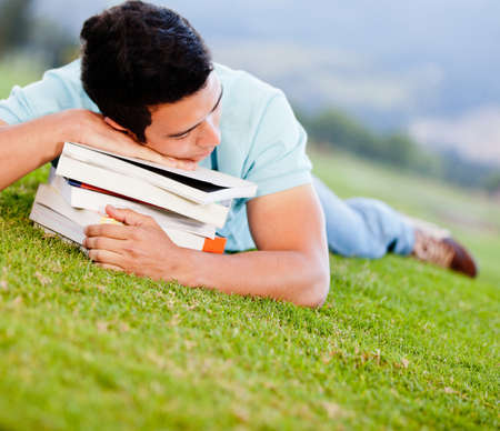 Tired male student  sleeping on top of books outdoors  photo