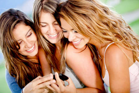 sms text: Gossip girls looking at a cell phone and smiling  Stock Photo