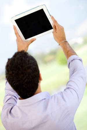 Man looking at the screen of a tablet computer - outdoors  photo