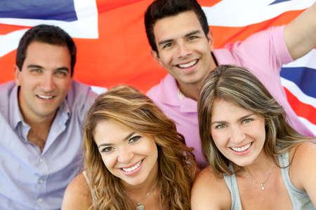 bandera inglesa: Grupo brit�nico de las personas con la bandera de la Uni�n Foto de archivo