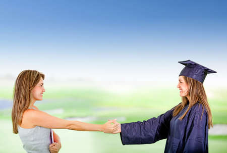 Female student giving a handshake to her graduate self - education concepts  Stock Photo - 12393802
