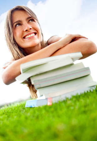 Pensive female student lying outdoors on a pile of books  photo