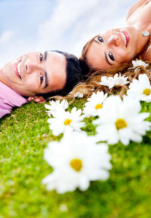 Beautiful loving couple lying outdoors in a garden of daisies  photo