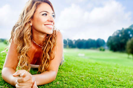 latin people: Beautiful woman lying on the floor at the park  Stock Photo