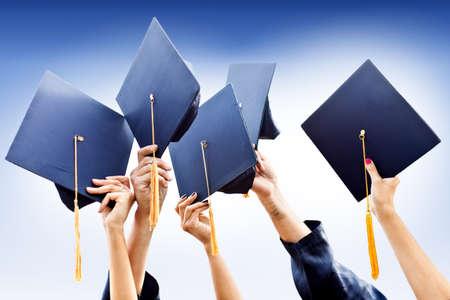 absolwent: Grupa ludzi rzucających kapelusze ukończeniu studiów w powietrzu
