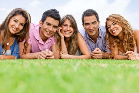 Group of people lying outdoors and smiling  photo