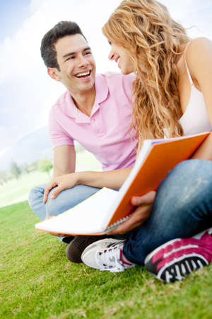 Couple of students sitting outdoors talking and laughing  Stock Photo - 12393867