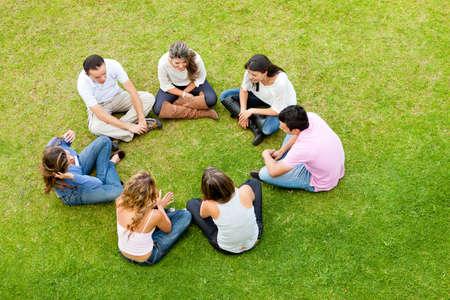mensen kring: Groep vrienden zitten in een kring buiten
