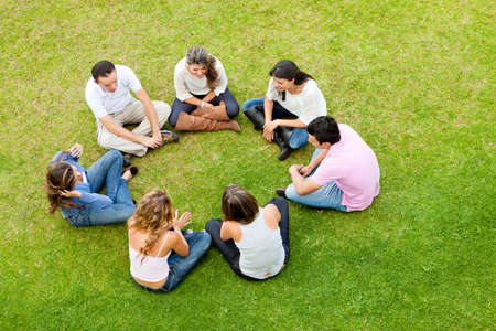 friendship circle: Group of friends sitting down in a circle outdoors