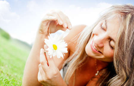 loves: Woman with a daisy flower playing he loves me or not