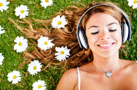 Woman listening to music with headphones outdoors  photo