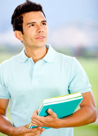 hispanic male: Thoughtful male student holding notebooks and looking up