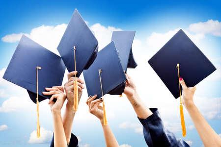 licenciatura: Grupo de personas que lanzan irreconocible graduaciones sombreros en el aire Foto de archivo