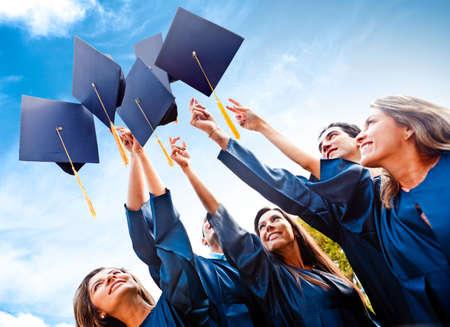 gorros de graduacion: Los estudiantes lanzando sombreros de graduaci�n en el aire la celebraci�n de
