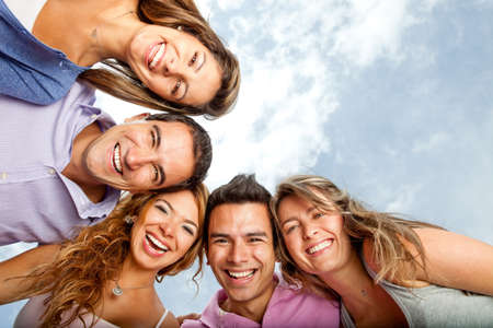 friends hugging: Group of young people hugging and laughing  Stock Photo