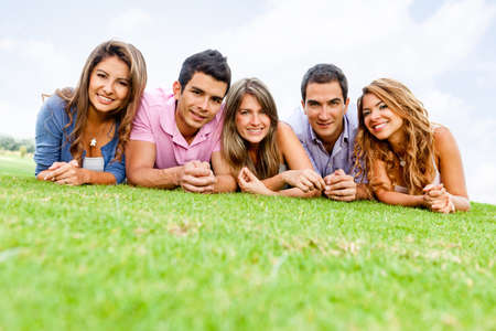 male friends: Group of young people lying outdoors smiling