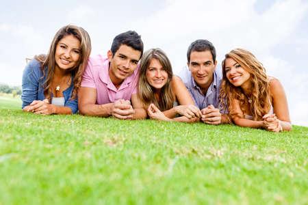 grupo de hombres: Grupo de j�venes se extiende al aire libre sonriente