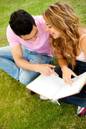 Young couple studying outdoors while having fun  photo