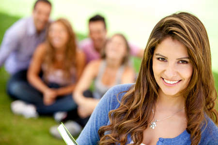 Female student smiling outdoors with a group of friends  photo