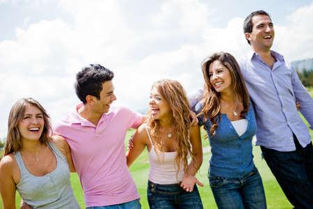 giggle: Feliz grupo de amigos se divierten y sonriente en el parque