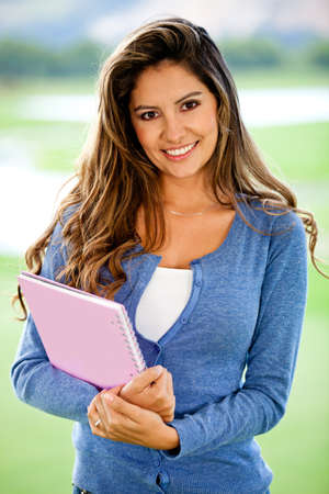 Happy female student smiling and holding a notebook - outdoors  photo